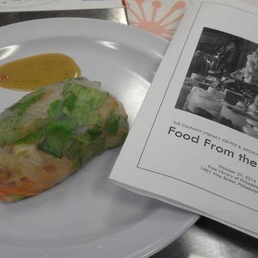 a freshly made spring roll and a program from the Food from the Archives event