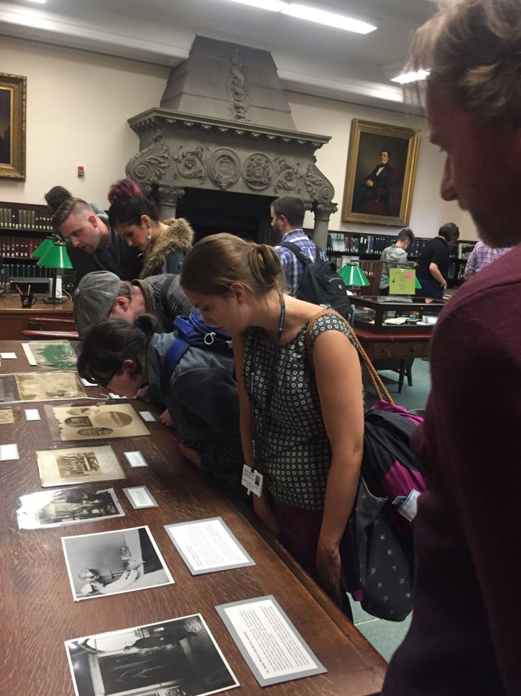 visitors looking at photographs on display
