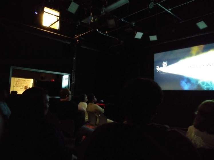Audience viewing film on a screen in a darkened room.