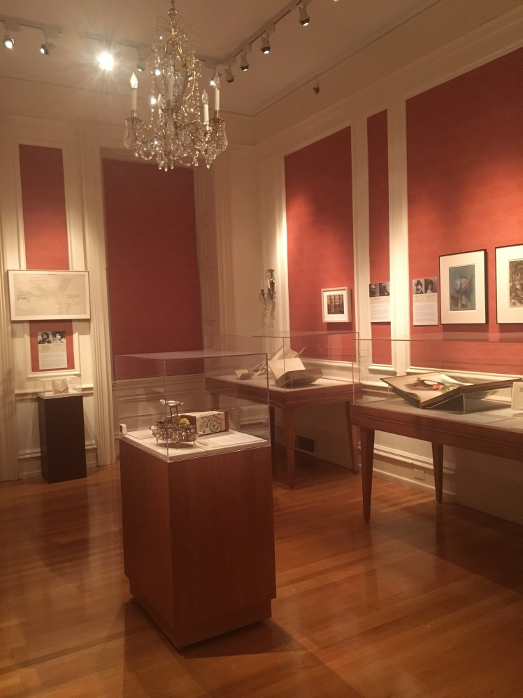 Exhibit at the Rosenbach. Books in class cases with crystal chandelier hanging from center of the room.
