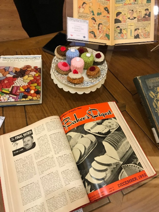 Cupcakes and books laid on a table.