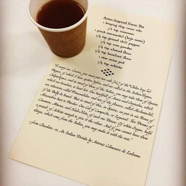 Coffee cup resting on drink recipe for Aztec-Inspired Cacao Tea printed on parchment looking paper in decorative print.