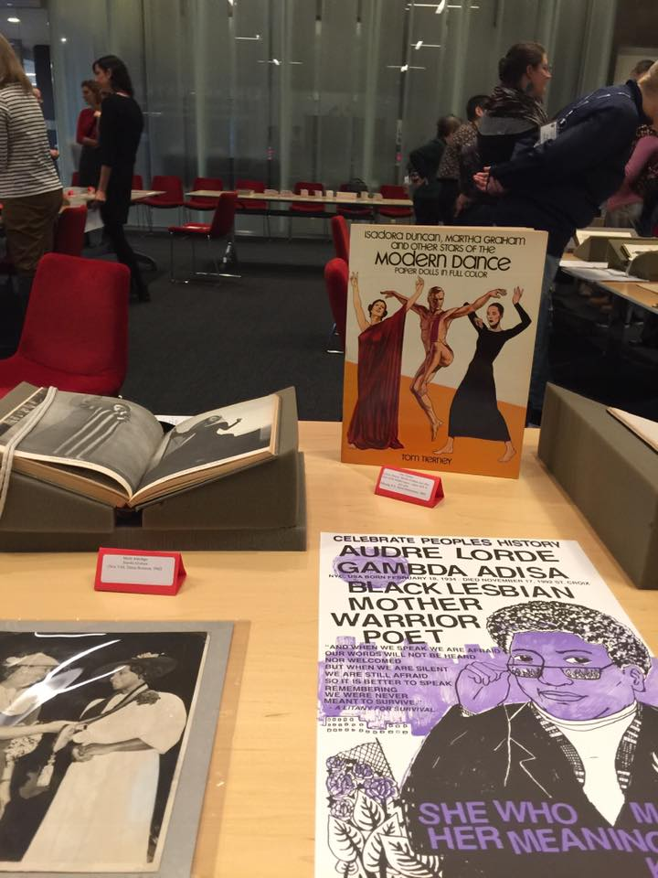 Book on modern dance, Audre Lorde poster, open book, and photo of 2 women on display on a table.